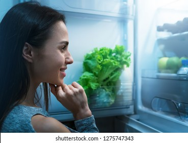 Photo of young woman having opened fridge deciding what to eat at night
