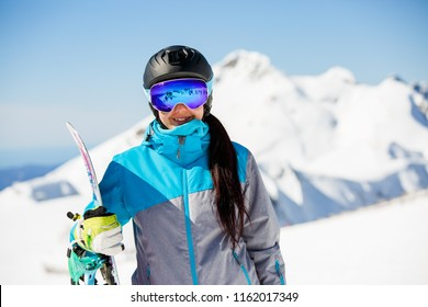 Photo of young woman in helmet wearing sunglasses, with snowboard on background of snow mountains