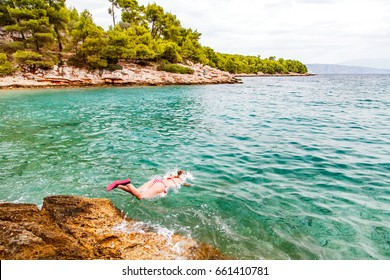 Photo of young woman jumping in the water