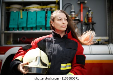 Photo of young woman with long hair looking to side next to fire engine