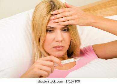 Photo of young woman lying in bed and looking at thermometer reading