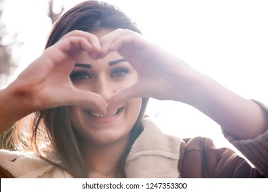Photo of  young woman making heart hand sign over her face with feeling love