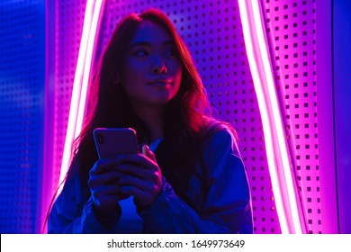 Photo of young woman posing over neon lights using mobile phone.