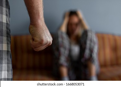Photo of young woman sitting on sofa at home,focus is on man's fist in the foreground of the image.Home violence concept.Frightened woman and men's fist.Woman is victim of domestic violence and abuse.