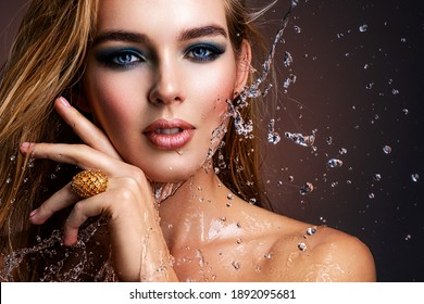 Photo of young woman with style make-up and water splashes  . Portrait of blonde woman with drops of water around her face. Sexy girl with blue eye makeup. Fashion model and water. Fashion concept.