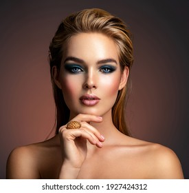 Photo of young woman with style make-up. Portrait of blonde woman with a beautiful face. Closeup face with stylish blue makeup. Fashion model with long hair, studio shot. Fashion concept.