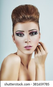Photo of a young woman with stylish makeup isolated on cyan.