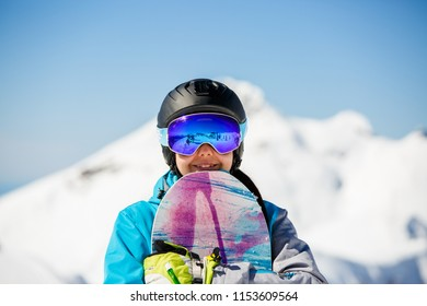 Photo of young woman tourist in helmet looking into camera with snowboard in hands