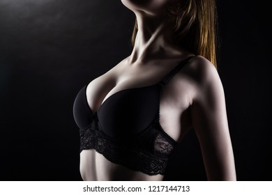 Photo of young woman's breast in black underwear