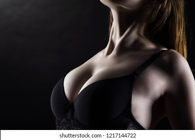 Photo of young woman's breast in black lingerie