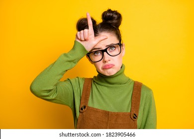 Photo of youngster student lady two buns bad mood grimacing show loser symbol forehead offended classmates bully her wear specs green pullover brown overall isolated yellow color background
