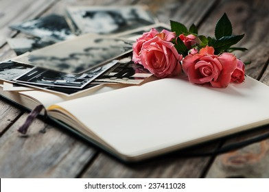 Photoalbum with pink rose on Wooden table