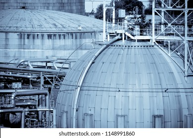 Photoartistic representation of a storage area in a chemical plant, comprising flat bottom tanks and spherical tanks.