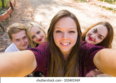 Photobomb performed by her good friends while she took a selfie for social network - the camera's point of view.