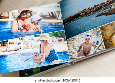Photobook album on deck table with travel photos
