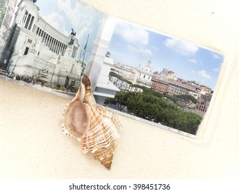 the photobook and big cockleshell are on white sand, a close up
