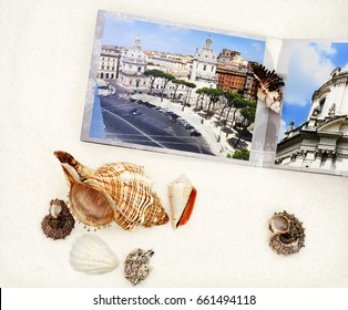 the photobook and cockleshells are on white sand, a close up