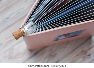 photobook and flash drive with a box photobook in a leather cover Open photo book pages photo album on a wooden background