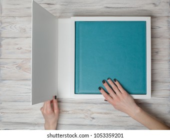 photobook in hands. Photo album in cardboard box. open box with photo album.  photobook in a gift cardboard box a woman holds a family  photobook. a person opens a photobook.