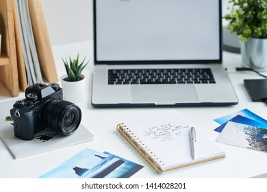 Photocamera on copybook, laptop, some photos, notebook with notes and pen on workplace of creative designer or photographer