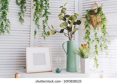 Photoframe, vase, hourglass, plants and various decorative objects on a table in a brightly lit room in summer