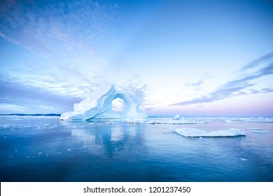 Photogenic and intricate iceberg with a hole under an interesting and colorful sky during sunrise with full moon. Disko bay, Greenland.