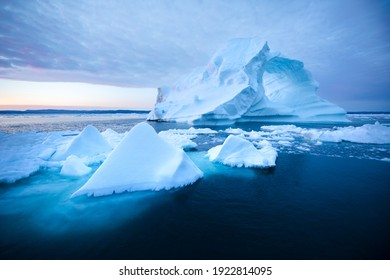 Photogenic and intricate iceberg with a hole under an interesting and colorful sky during sunrise. Disko bay, Greenland.