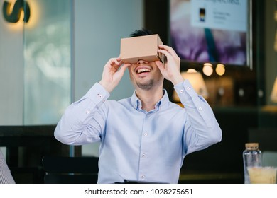 A photogenic, young Chinese man tries on Virtual Reality goggles and is smiling and delighted as he tries it for the first time.