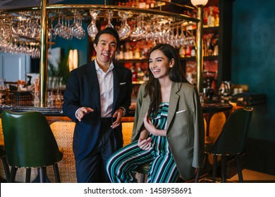 A photogenic young diverse Asian couple enjoy a drink at a classy bar. A Chinese man in a well-tailored and professional suit is talking with an elegant Indian woman who is laughing out loud.