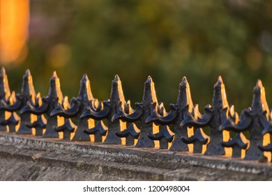 A photograp of ornate iron spikes on top of an old wall at sunset