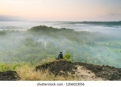 A photograper sitting and capturing beautiful scenery of a misty forest