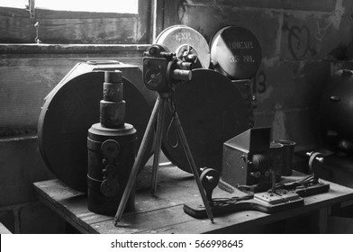 A photograph of antique projection room equipment consisting of vintage 35 mm movie cameras, canister reels, reel slicing machine and other equipment.