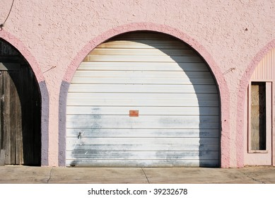 A photograph of a arched garage door with pink and purple walls in a street alley.