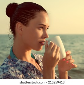 Photograph of a beautiful brunette woman with white mug with tea or coffee relaxing on a beach, with a retro toning effect.