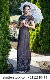 Photograph of a beautiful girl in a dress with an umbrella from the sun in the park.