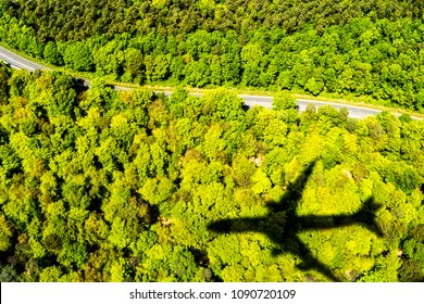 Photograph of a black plane shadow or silhouette on the bright green forest treetops and curved road below on a sunny day making a great travel or transportation background.