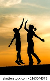 Photograph of a boy and a teen girl silhouetted at sunset jump up and give each other a high five.