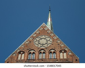 Photograph of the brick gable with church tower, roof, ornaments and different windows of the cathedral in Bad Doberan in Mecklenburg-Vorpommern, Germany in front of a clear blue sky in summer.