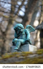 photograph of a bronze sculpture (statue) of a child angel in Père Lachaise cemetery (in Paris). The angel is holding his head with one hand.