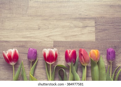 Photograph of a bunch of tulips on wooden surface