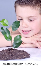 photograph of a child contemplating a plant