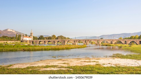 Photograph of church and city bridge with name Lime Bridge, Portugal