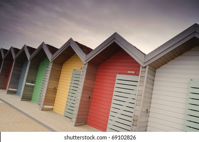 Photograph of colorful beach huts under a slightly moody sky.