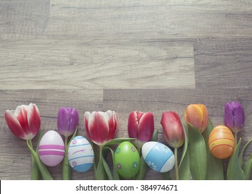 Photograph of a couple of colorful easter eggs with a bunch of tulips on wooden surface