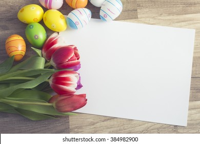 Photograph of a couple of colorful easter eggs with a bunch of tulips alligned around a sheet of white paper with copy-space on wooden surface
