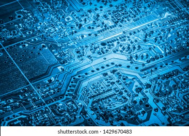 Photograph of dark Marine blue colored computer microcircuit motherboard vignette detail