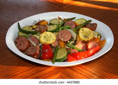 A photograph of a dish that includes asparagus, sausage, squash, peppers and onions.