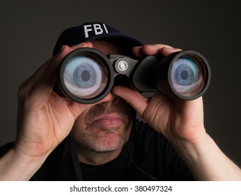 Photograph of an FBI agent in t shirt and baseball cap looking through binoculars with large, cartoonish eyes in the lenses.