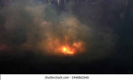 A photograph of fireworks being set off at a street festival in Taiwan with smoke, debris and noise abstracting the image.