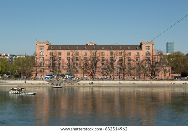 A photograph of the former Army Barracks (Kaserne) in Basel, Switzerland. One of the non-motorized ferries can be seen on the Rhine river in the foreground.